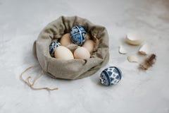 Pascua pintó los huevos en un bolso de la lona en un fondo gris imágenes de archivo libres de regalías