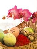 Pascua y huevos de codornices en una cesta con la orquídea Foto de archivo libre de regalías