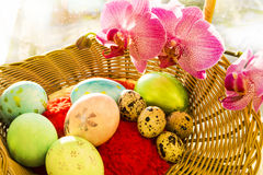 Pascua y huevos de codornices en una cesta de mimbre con Imagen de archivo