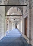 Pase en la mezquita de Nuruosmaniye, con las columnas, los arcos y el piso cubiertos con la alfombra azul encendida por las venta Foto de archivo libre de regalías