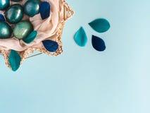 Pasen-achtergrond met eieren in blauw worden verfraaid, turkoois en gouden in nest met veren die De ruimte van het exemplaar royalty-vrije stock foto