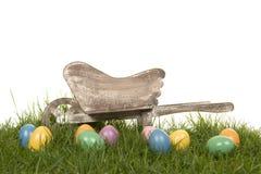 Pasen-achtergrond met gekleurde eieren in het gras en een houten kruiwagen Stock Afbeelding