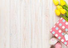 Pasen-achtergrond met kleurrijke eieren en gele tulpen Stock Afbeeldingen