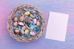 Pasen-achtergrond met kleurrijke kwartelseieren, veren in een rieten mand en een leeg document dichtbij het, hoogste mening De ru Royalty-vrije Stock Foto