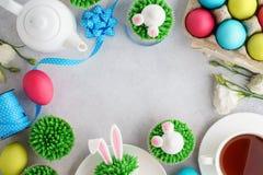 Pasen-achtergrond met konijntje cupcakes, thee en geschilderde eieren stock afbeelding