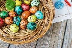 Pasen-achtergrond met paaseieren in de mand en de lentebloemen Stock Afbeeldingen