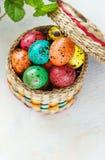 Pasen-achtergrond met paaseieren in de mand en de lentebloemen Royalty-vrije Stock Afbeelding