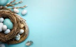 Pasen-achtergrond met paaseieren en de lentebloemen op blauw t Royalty-vrije Stock Afbeeldingen