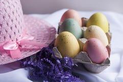 Pasen-bonnet met gekleurde eieren en purper gras Stock Afbeelding