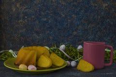 Pasen-brood op groene plaat, roze mok en geschilderde paaseieren royalty-vrije stock foto's