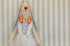 Pasen Bunny Rabbit, Handmeisje Toy Voor een lichte gestreepte achtergrond, exemplaarruimte voor uw gelukwensen op de Pasen-vakant royalty-vrije stock foto