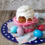 Pasen-cake - kulich Het traditionele zoete brood van Pasen verfraaide wit suikerglazuur en kleurde eieren op blauw servet op hout stock fotografie