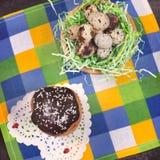 Pasen-cake met chocoladesuikerglazuur en een nest met kwartelseieren op a stock foto