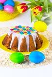 Pasen-cake met witte glans op een gele plaat Stock Foto's