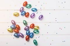 Pasen-chocolade minieieren die in kleurrijke folie worden verpakt, die op een witte houten achtergrond wordt verspreid, hoogste m stock foto's