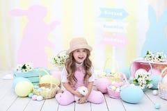 Pasen-concept en familievakantie! Meisje het spelen met Pasen-konijntje Het kleurrijke decor van Pasen in de studio, een mand van royalty-vrije stock foto
