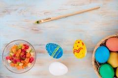 Pasen-concept gekleurde eieren naast gekonfijte vruchten en borstel op een houten bacground Royalty-vrije Stock Afbeelding