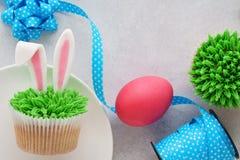 Pasen-concept met konijntjesoren cupcakes, blauw lint, roze ei stock fotografie