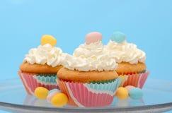 Pasen cupcakes met de pastelkleur gekleurde eieren dat van het chocoladesuikergoed wordt bedekt Stock Fotografie