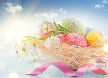 Pasen-de achtergrond van de vakantiescène Traditionele kleurrijke eieren en de lentebloemen in het nest over blauwe hemel Royalty-vrije Stock Afbeeldingen
