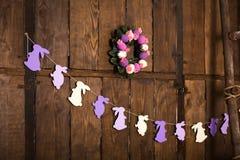 Pasen-decor Kroon met en eieren van purpere en witte kleur, slinger met konijnen tegen de achtergrond van een muur van donker hou royalty-vrije stock foto
