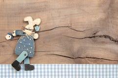 Pasen-decoratie met een blauw konijntje op een houten achtergrond in sh Stock Foto's