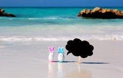 Pasen, estereggs op het strand, het zand, de oceaan en het overzees Stock Foto