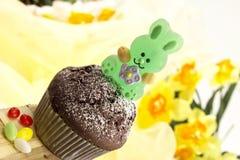 Pasen-gebakje, chocolademuffin met het konijntje van suikerpasen, suikereieren Stock Foto's