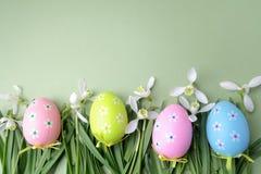 Pasen gekleurde eieren in het gras op groene achtergrond Hoogste mening Stock Fotografie