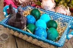 Pasen gekleurde eieren, stro, bloemen Stock Foto's