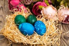 Pasen gekleurde eieren, stro, bloemen Royalty-vrije Stock Afbeeldingen