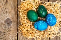 Pasen gekleurde eieren, stro, bloemen Royalty-vrije Stock Afbeelding