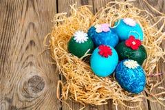 Pasen gekleurde eieren, stro, bloemen Stock Fotografie