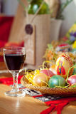 Pasen geschilderd eieren en wijnglas op lijst Stock Afbeelding