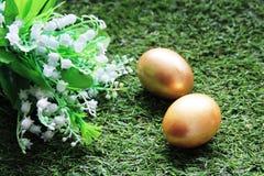 Pasen Geschilderd met Gouden eieren op gras Stock Fotografie