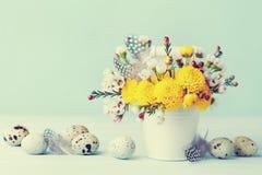 Pasen-groetkaart met kleurrijke bloemen, veer en kwartelseieren op uitstekende blauwe achtergrond Mooie de lentesamenstelling Royalty-vrije Stock Afbeelding