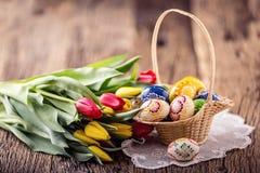 Pasen Hand - gemaakte geschilderde paaseieren in mand en de lentetulpen Royalty-vrije Stock Foto