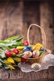 Pasen Hand - gemaakte geschilderde paaseieren in mand en de lentetulpen Stock Foto's