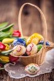 Pasen Hand - gemaakte geschilderde paaseieren in mand en de lentetulpen Stock Afbeeldingen