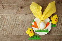 Pasen-het concept van de kinderenkaart met ei in konijntje nupkin, witte plaat en document ambacht diy decoratieve chikens op hou stock foto's