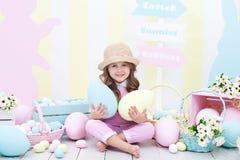 Pasen! het meisje houdt grote multi-colored eieren in haar handen tegen de achtergrond van het Pasen-binnenland Een leuke baby ac royalty-vrije stock afbeelding