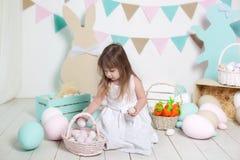 Pasen! Het mooie meisje in een witte kleding legt paaseieren in een mand Vele verschillende kleurrijke paaseieren, kleurrijke int stock fotografie