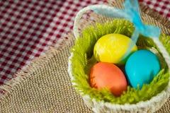 Pasen kleurde eieren in een mand op een canvasservet en een geruit tafelkleed royalty-vrije stock foto's