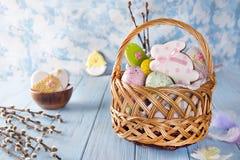 Pasen-koekjes, konijntjes en Multicolored paaseieren in een mand op lichtblauwe achtergrond Royalty-vrije Stock Foto
