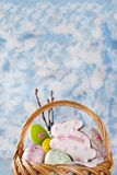 Pasen-koekjes, konijntjes en Multicolored paaseieren in een mand op lichtblauwe achtergrond Royalty-vrije Stock Afbeeldingen