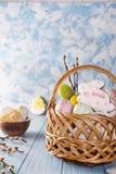 Pasen-koekjes, konijntjes en Multicolored paaseieren in een mand op lichtblauwe achtergrond Royalty-vrije Stock Foto's