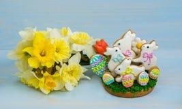 Pasen-koekjes wit konijntje en gekleurde eieren met een boeket van ye Stock Foto