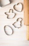 Pasen-koekjessnijder: het konijn, de kip, het ei, het hart en het deeg rollen op witte houten achtergrond, hoogste mening Royalty-vrije Stock Foto