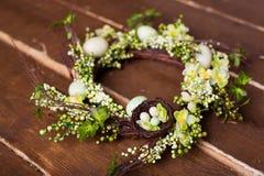 Pasen-kroon met bloemen en eieren op een houten achtergrond Stock Foto's