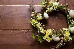 Pasen-kroon met bloemen en eieren op een houten achtergrond Royalty-vrije Stock Fotografie